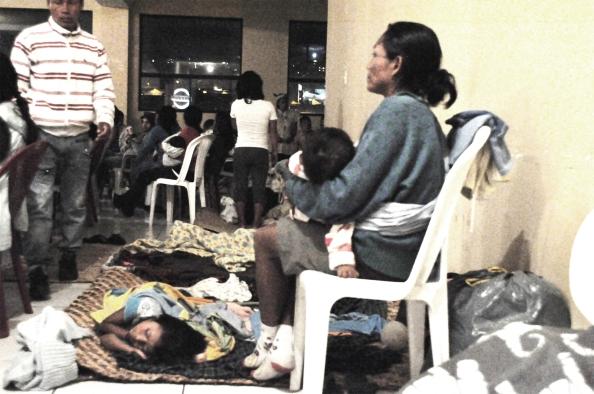 Una mujer cuida a sus niños mientras escucha un recital del Chamo Guevara en la sede de la CONAIE